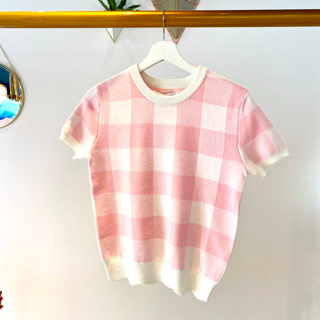 UNIKONCEPT: Lifestyle boutique; image shows a gingham tee shirt by English factory. The Jolie knit gingham tee features short sleeves, a crewneck collar and a wide white elastic band at the waistline of the shirt. It is a white base with a light pink over top.