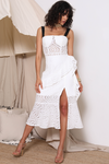 Bridal wear: Model wears a white midi length lace dress with a slit on the left leg. The dress is lined from the waist to mid thigh and has lining in the breast pads. The dress has black straps. The Nuka Dress is a stunning piece to add to your wedding events.