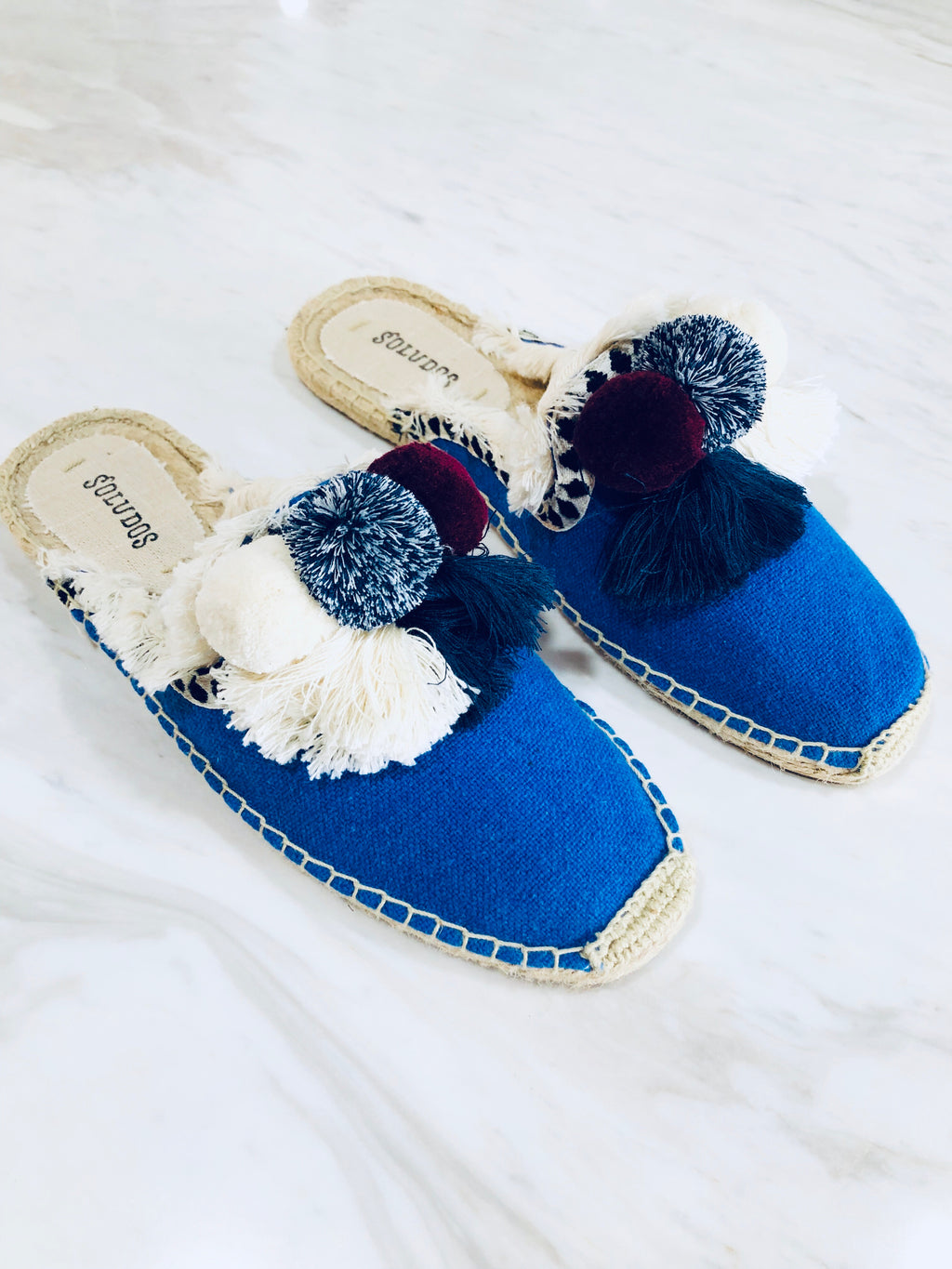 UNIKONCEPT Lifestyle boutique: Image shows a pair of mule soludos. The coco pom pom mules in marlin blue features a canvas blue toe piece with white, Burgundy and light blue pom poms on top. the shoe also has tassel underneath the poms and intricate embroidered detail around.