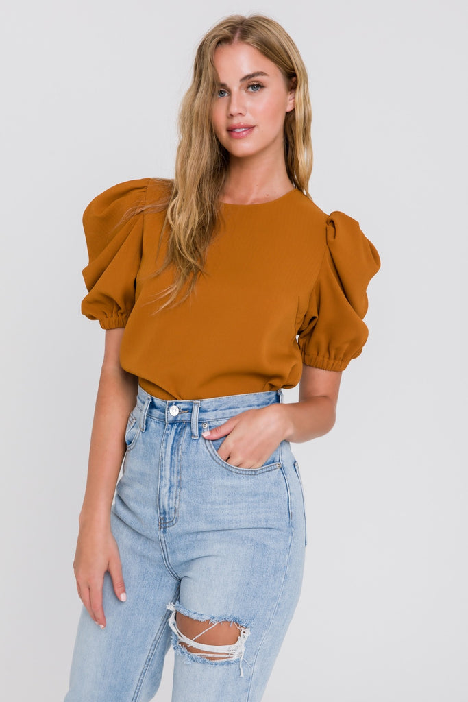 UNIKONCEPT Lifestyle boutique; image shows the Kate Top in a cognac brown by English Factory. This relaxed fitting tee is made of a ribbed fabric with highly elevated puff sleeves finished off with an elasticized cuff. The shirt has a button closure at the top of the back.