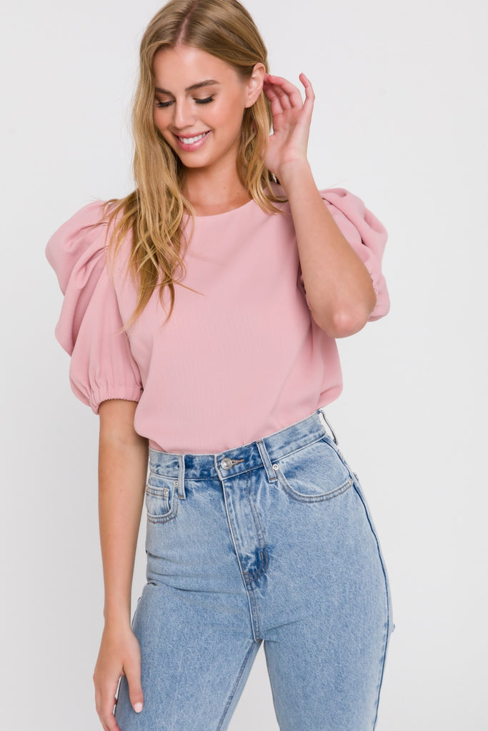 UNIKONCEPT Lifestyle boutique; image shows the Kate Top in pink by English Factory. This relaxed fitting tee is made of a ribbed fabric with highly elevated puff sleeves finished off with an elasticized cuff. The shirt has a button closure at the top of the back.