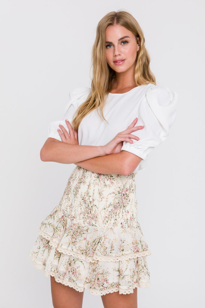 UNIKONCEPT Lifestyle boutique; image shows the Vivienne Skirt by English Factory. This skirt is made of a nude fabric featuring a neutral dainty floral print. The skirt features a fitted elasticized drop waist fit with a tiered ruffle hem. The hems of the ruffles feature a lace trim.