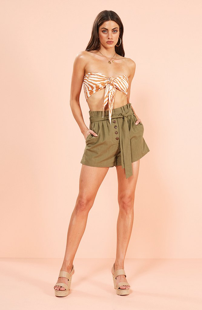 Model wears a pair of Minkpink olive paperbag linen shorts. The linen paperbag short in the colour khaki comes with a high waist and brown vintage buttons and an olive belt.