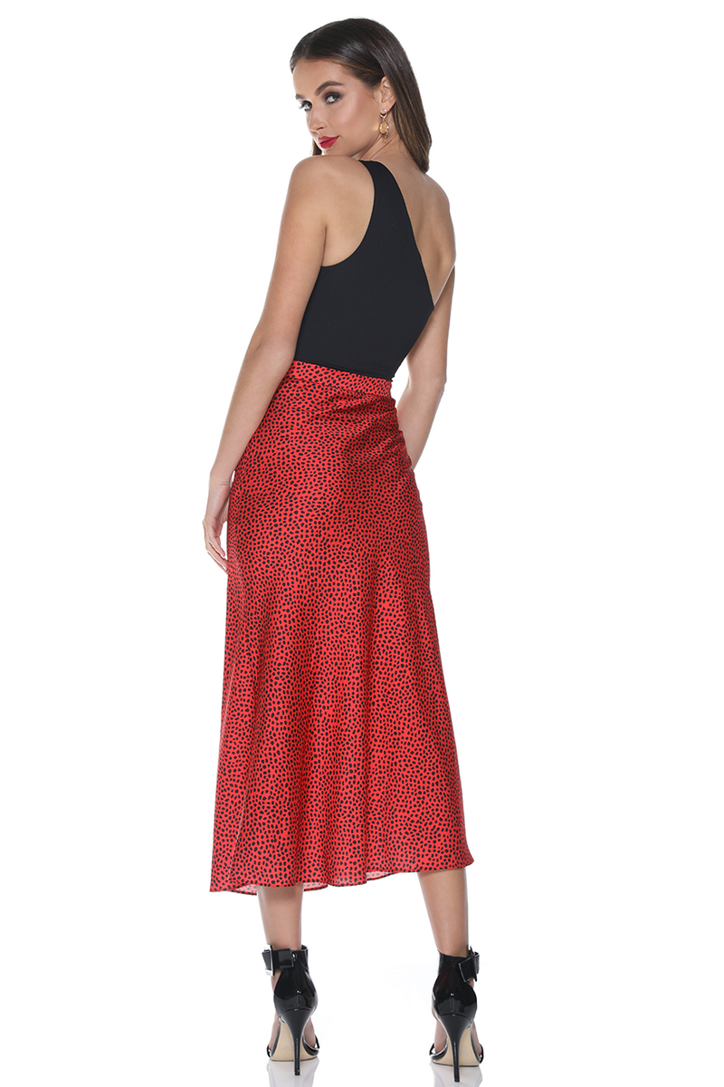 UNIKONCEPT: Lifestyle boutique; image shows a red based slip skirt with a red and black polo dotted pattern. Runaway created the perfect skirt when making the Kendra slip skirt it features a side zipper for easy dressing and removal, it is midi length and has a black polka dotted print throughout.