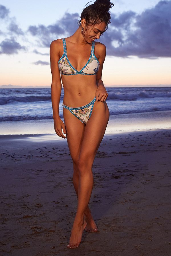 Front view of model wearing triangle bikini top in a blue on white floral print featuring a contrasting 1 inch blue waist band with decorative stitching. The front features 1 inch straps and a triangle cut front and back clasp closure.