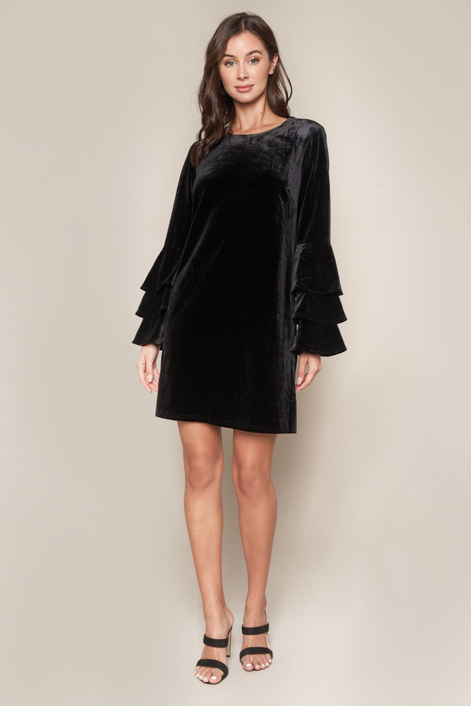 UNIKONCEPT: Lifestyle boutique; Image shows a black velvet mini dress by sugar lips. The Blair bell sleeve is a perfect velvet, black holiday dress. It features a three quarter length arm with two layers of ruffles on either side, making the sleeves a bell shape. It also has a key hole back and a scoop neckline.