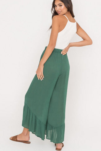 UNIKONCEPT Lifestyle boutique: Model is wearing dark green culotte styled pants. The Verte culottes by Lush are cropped in length have subtle ruffles at the bottom, they are high waisted and tie at the top.