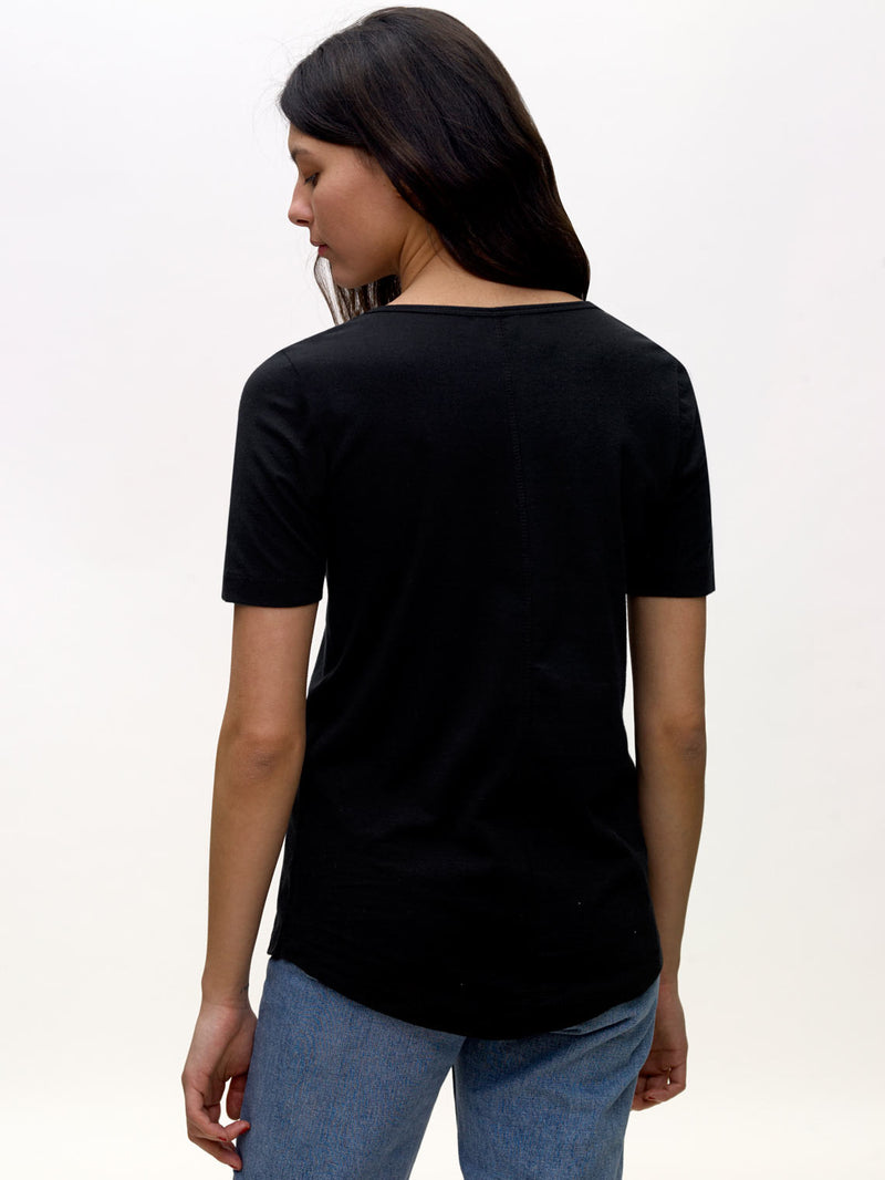 Model wearing black, v-neck, KOTN t-shirt. View of Models back.