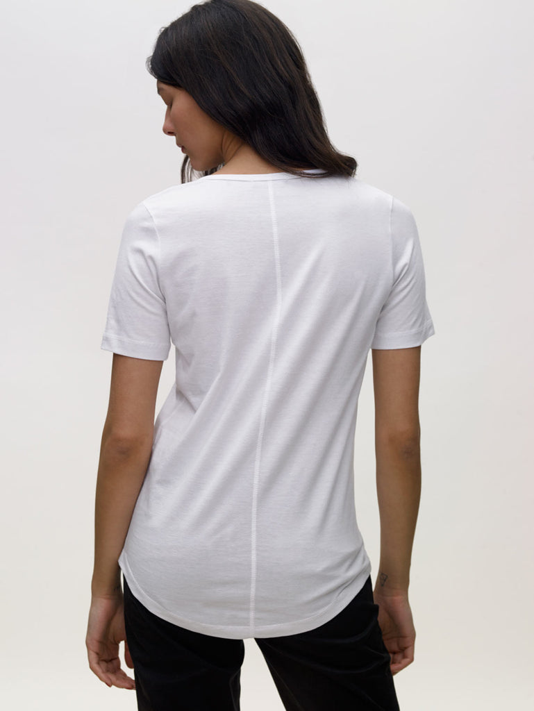 Model wearing white, v neck, KOTN t-shirt. View of Models back.