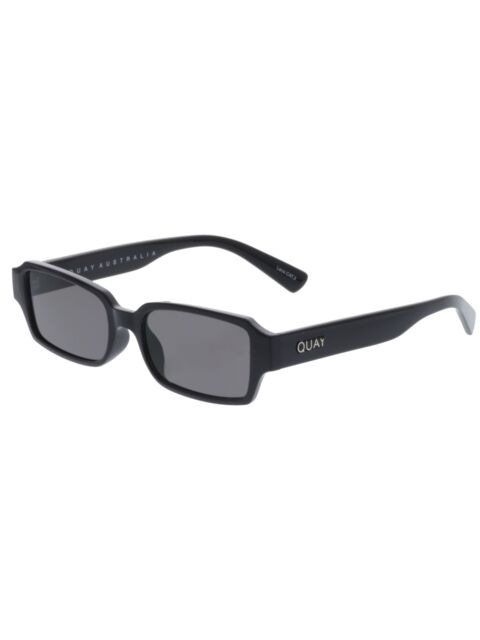 Image shows a pair of slender rectangular Quay sunglasses. The strange love sunnies are blacked out with black frames and a dark smoke lens.