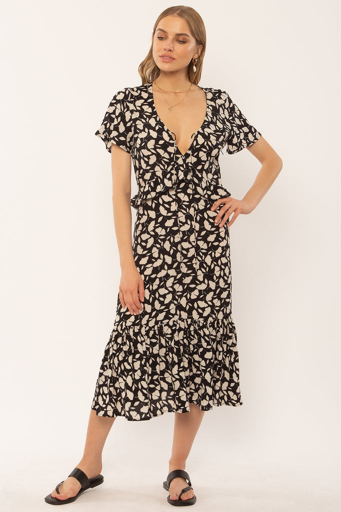 UNIKONCEPT: Lifestyle boutique; image shows a tee shirt styled midi dress by amuse society. This dress features a light plunge v neckline with ruffled detailing, a small tied bust section and ruffle detailing at the bottom. It is a small black and white floral pattern throughout and is a straight/ a line styled dress.