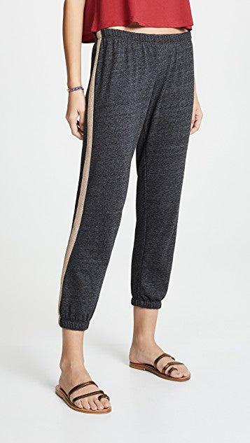 Model is wearing a pair of spiritual gangster sweatpants. The sparkle stripe perfect sweatpants are dark grey in colour with a gold sparkly stripe down either side of the pant. they have elastic bottoms for each leg and an elastic waistband .