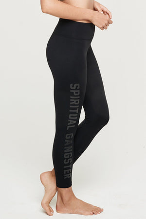 "Model wearing high waisted leggings, in black. Down the right front leg, ""Spiritual Gangster"" written in black glossy lettering."