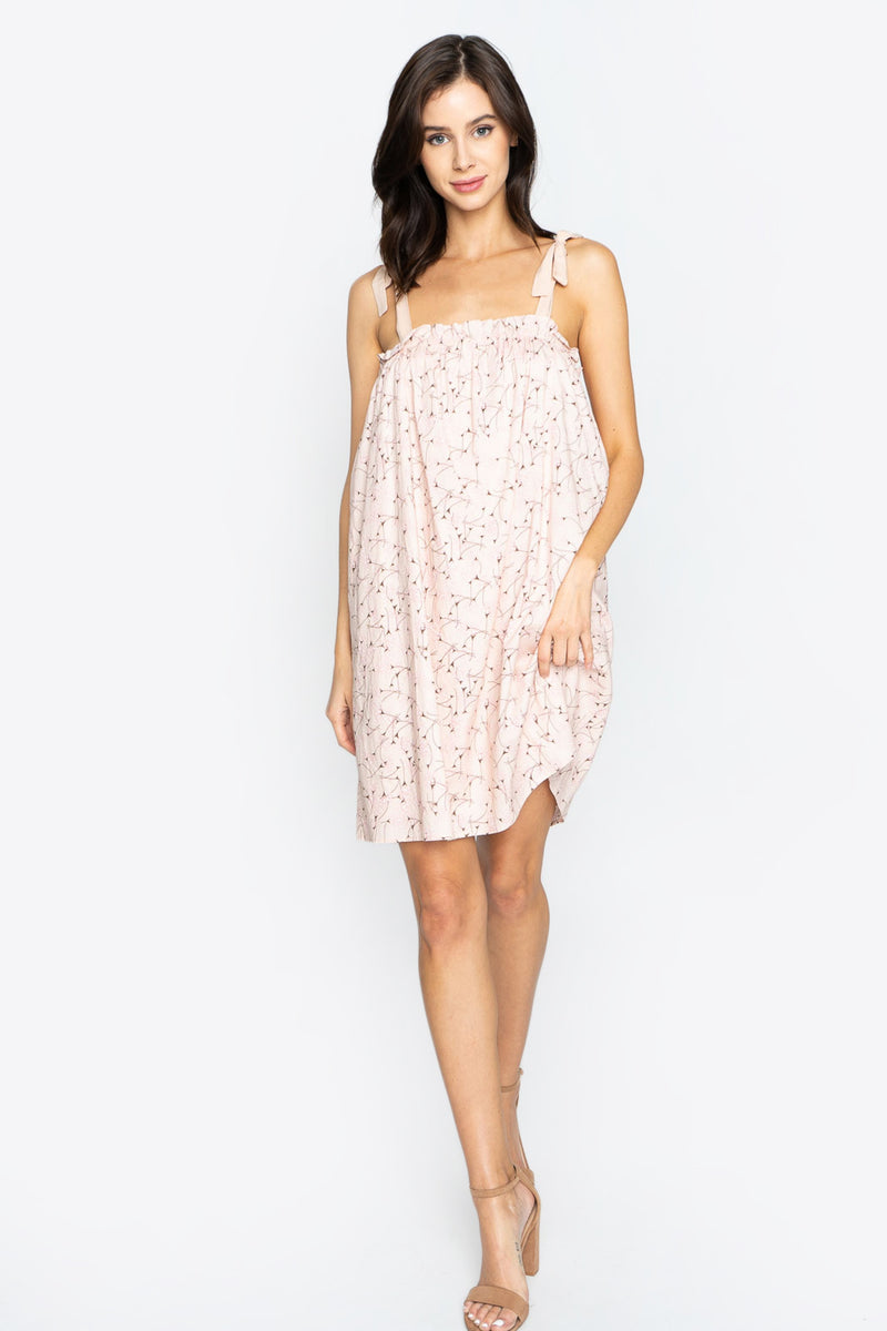 UNIKONCEPT Lifestyle boutique: Model wears a baby doll styled sugar lips dress. The Willem floral shift dress is a light pink colour with a darker pink  delicate floral print on top. The dress features self adjustable tie straps a ruffled top bodice and is about knee length.