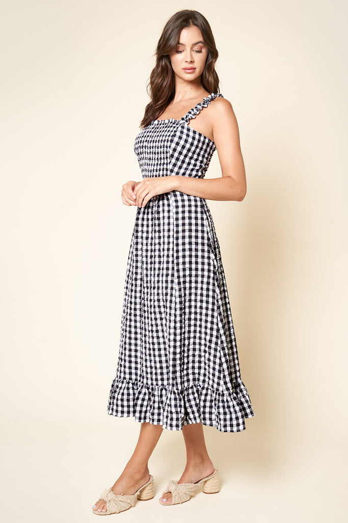 UNIKONCEPT Lifestyle boutique; image shows the London Gingham Midi Dress in black and white by SugarLips. The dress features a fitted bodice and relaxed a-line skirt with a ruffled bottom hem. The spaghetti straps also feature a ruffle detail. The fabric is made of a black and white checkerboard plaid pattern.