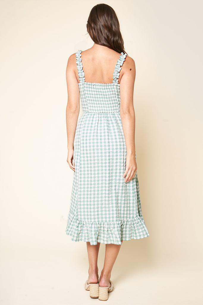 UNIKONCEPT Lifestyle boutique; image shows the London Gingham Midi Dress in mint and white by SugarLips. The dress features a fitted bodice and relaxed a-line skirt with a ruffled bottom hem. The spaghetti straps also feature a ruffle detail. The fabric is made of a mint and white checkerboard plaid pattern.