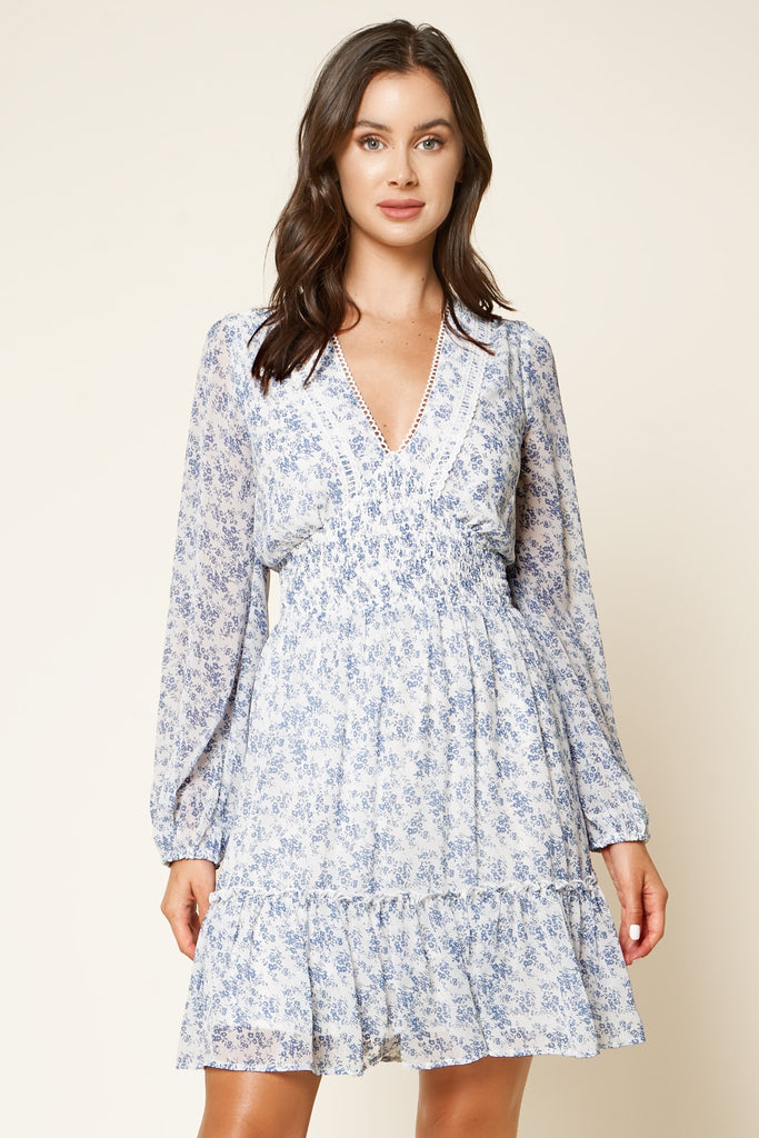 UNIKONCEPT Lifestyle boutique; image shows the Provence Dress in a blue floral print by SugarLips. This dress features a v-neckline and loose billowing sleeves. The waist is elasticized and fitted which flows into an a-line skirt with a ruffle hem. The neckline is trimmed with a dainty white lace. Fabric is a white base with an elegant blue floral print.