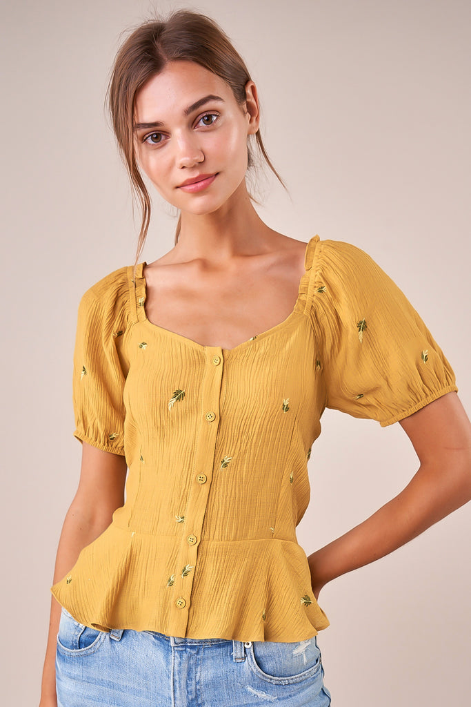 UNIKONCEPT: Lifestyle boutique; image shows a mustard yellow short sleeve peplum blouse by sugar lips. The Chasing highs embroidered peplum top features small embroidered florets throughout the top and button closures in the centre of the blouse. Can be worn on or off the shoulder.