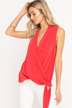 UNIKONCEPT Lifestyle boutique: Model is wearing a bright red lush blouse. The Ruby Lou blouse has thick straps, a criss cross mid section, it features a plunged neckline/ low V and a side tie bottom