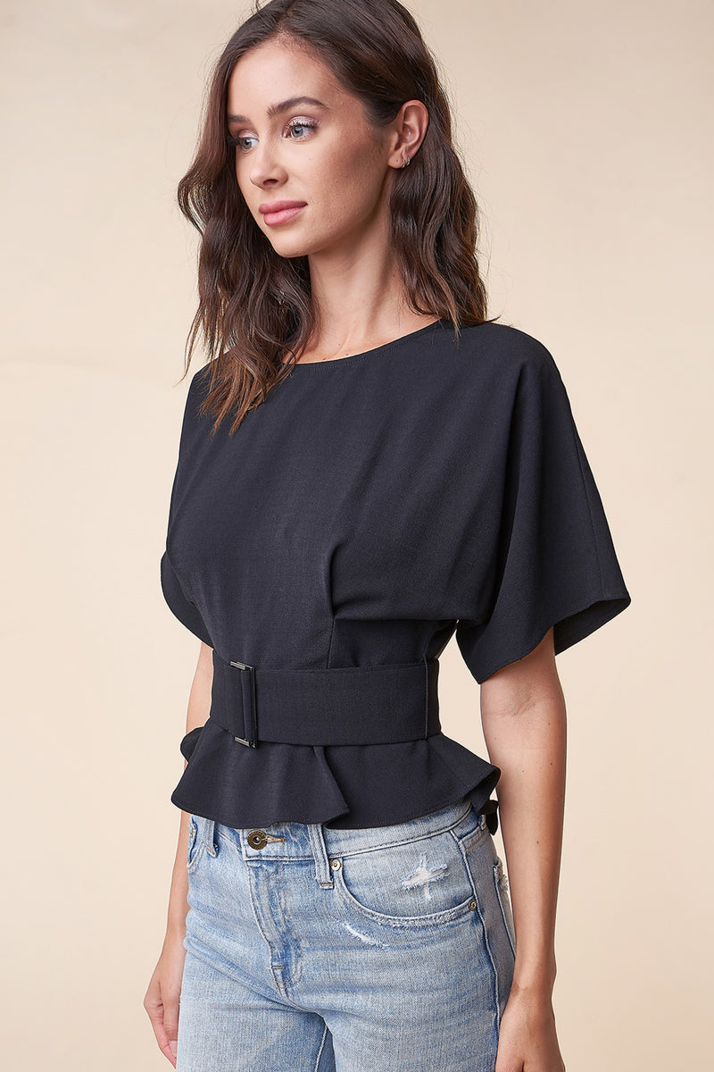 UNIKONCEPT Lifestyle boutique: Model is wearing the Rise Up Belted Blouse from Sugar Lips. The Rise Up Blouse is a black, peplum t-shirt with a wide d-ring belted waist. The back of the top features an open back with a button to secure the top and waist.