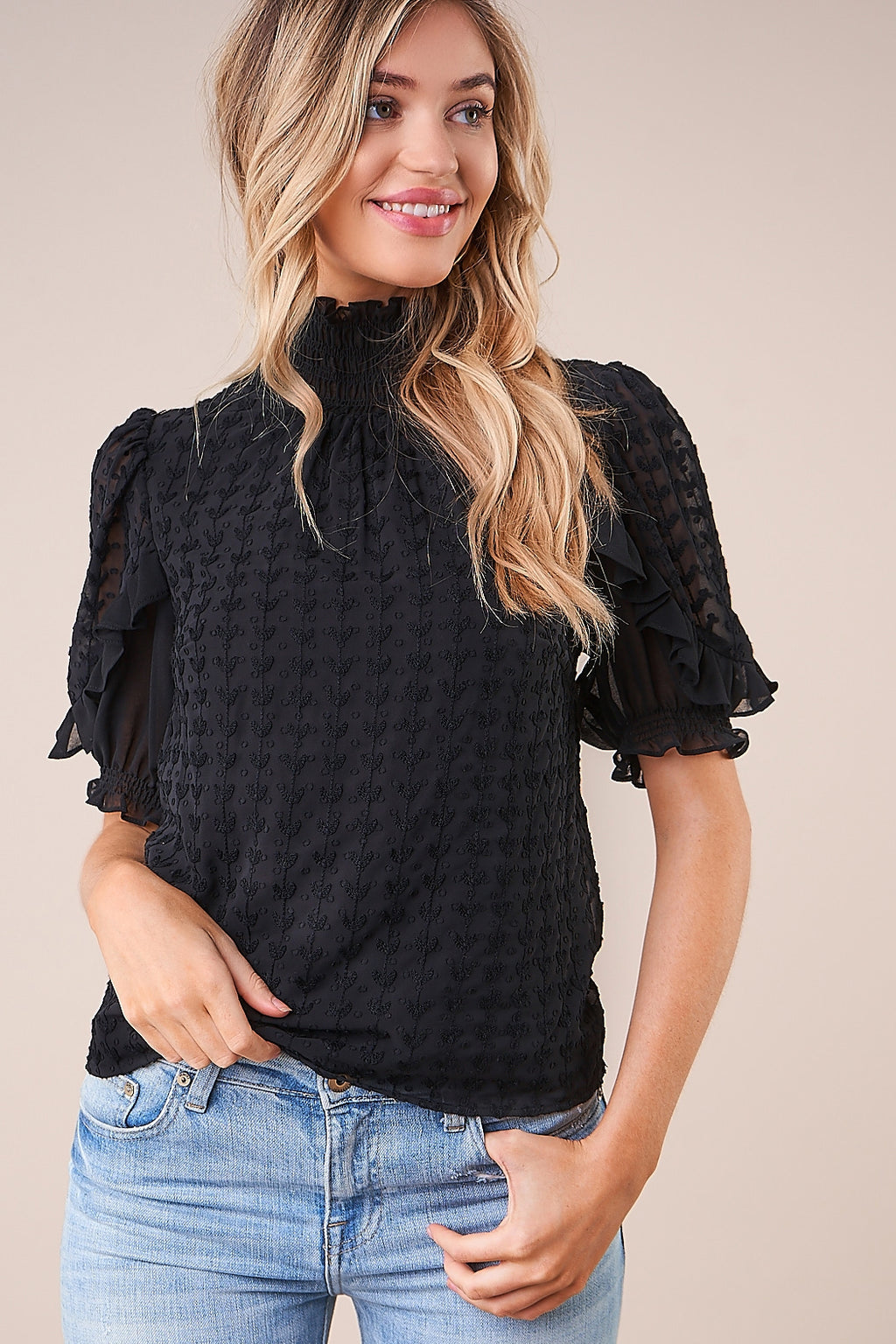 UNIKONCEPT: Lifestyle boutique; Image shows a mock neck short sleeved blouse by Sugar Lips. The Keep sake mock neck is a fully black top with transparent chiffon like fabric throughout. It features a puffed short sleeve and intricate detailing like polka dots and ruffles around the shoulders, elbow area and throughout the whole top.