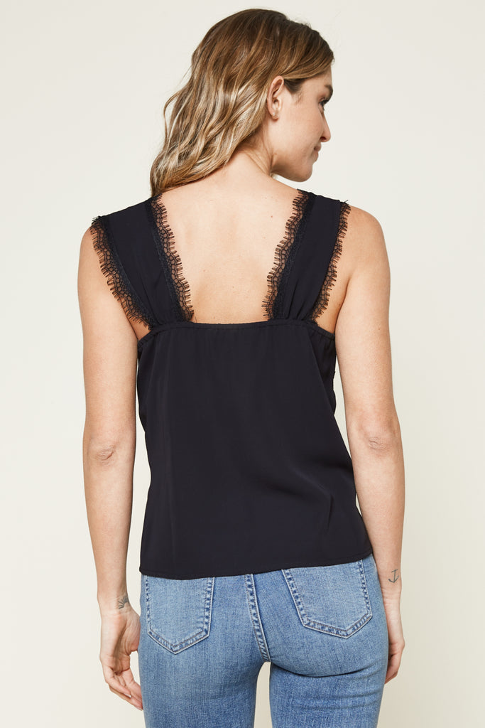 UNIKONCEPT Lifestyle boutique: image shows the Sutton Lace Trim Top in black by SugarLips. The top has cap sleeves and a tie detail along the front neckline. The square neckline and sleeves are trimmed with lace. The shirt is a relaxed pant length fit.