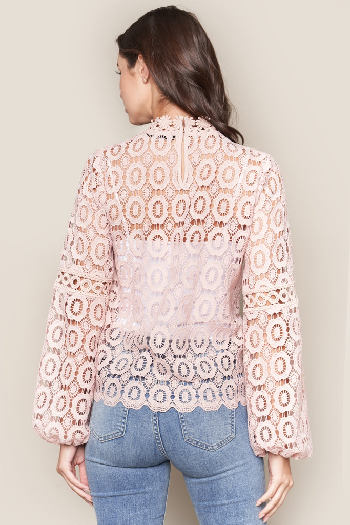 UNIKONCEPT: Lifestyle boutique; image shows a see through blush coloured lace, long sleeve top by sugar lips. The blush Santorini top features a mock neck and full long sleeves with a crocheted, lace detail throughout.