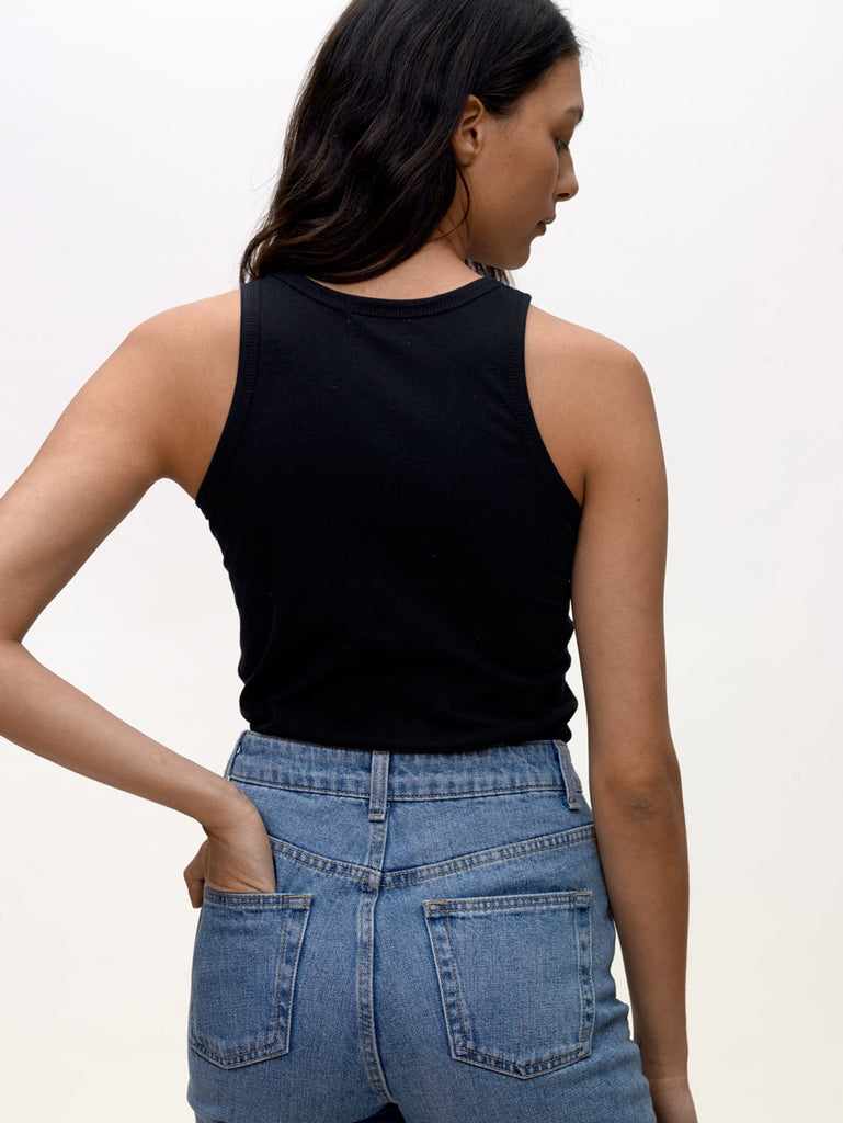 Model wearing Black, High neck slim KOTN Tank Top. View from the back.