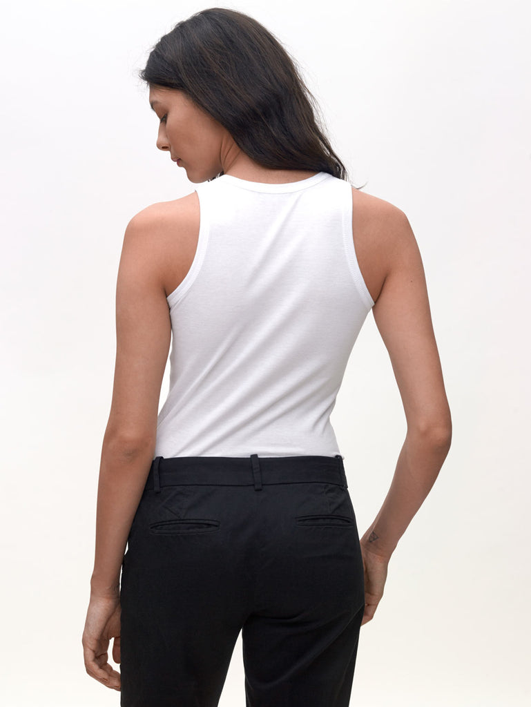 Model wearing White, High neck slim KOTN Tank Top. View of the back.