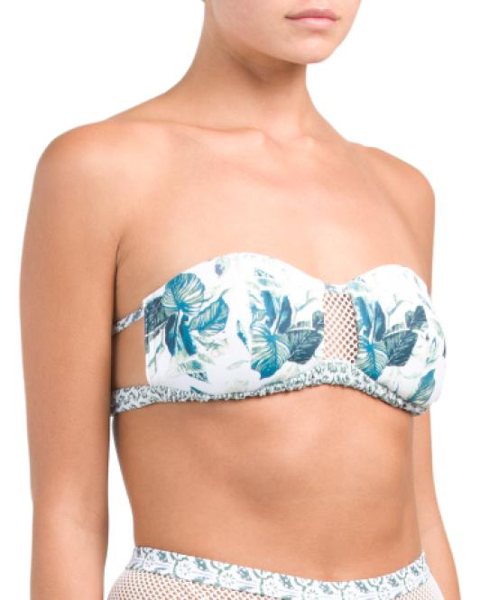 UNIKONCEPT Lifestyle boutique: Model is wearing a white strapless somedays loving bikini top. The emerald oasis bandeau top comes in a tropical greenery print, with a key hole of mesh fabric at the bust.