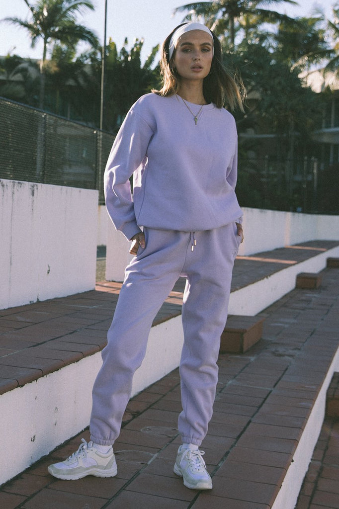 UNIKONCEPT Lifestyle boutique; image shows the Lilac Track Pants by Runaway. These high waisted tailored sweats feature an elasticized drawstring waist band, and elasticized ankle hems.