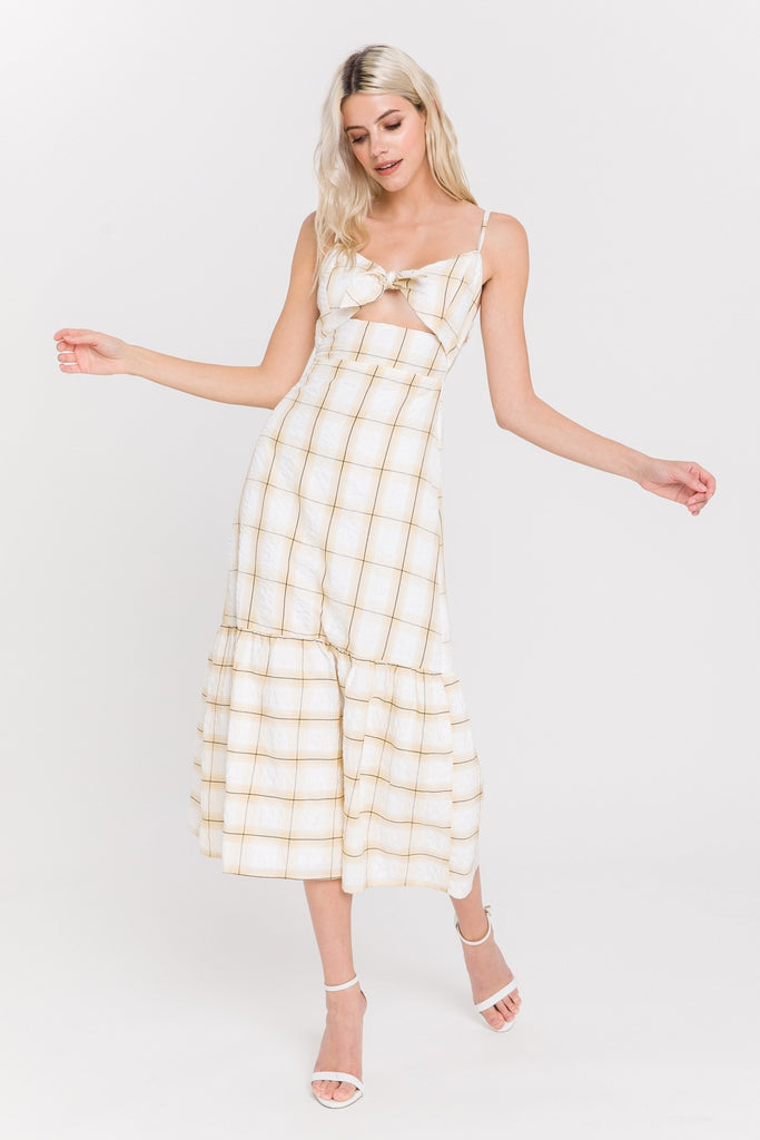 UNIKONCEPT Lifestyle boutique: the image shows the Marigold Check Print Maxi Dress. This adjustable spaghetti strap maxi dress features a cut out detail in the front of the dress accompanied by a tie detail in the middle of the chest. The colour of the dress is a yellow and black geometric square/check pattern on a white base. The skirt of the dress is free flowing with a billowed hem.