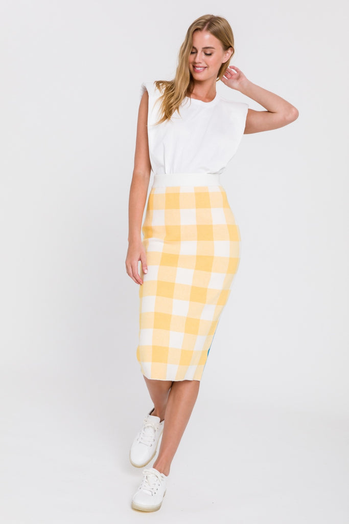 UNIKONCEPT Lifestyle boutique: Model is wearing a gingham print pencil skirt. The jasmine colour black skirt is made from a stretchy knit material. The front gingham print is a pale yellow and the back is a bright blue. The skirt is high waisted that is a midi length hitting the model right at the knees. This skirt was made by the Los Angeles designer, English Factory.