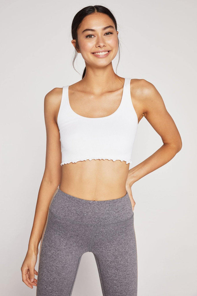 UNIKONCEPT Lifestyle boutique: Image shows the Amor Crop Tank in white by Spiritual Gangster. This cropped tank comes in an ultra soft ribbed seamless fabric. It features a flattering scoop neck, built-in shelf bra, and lettuce detailing at the bottom hem.