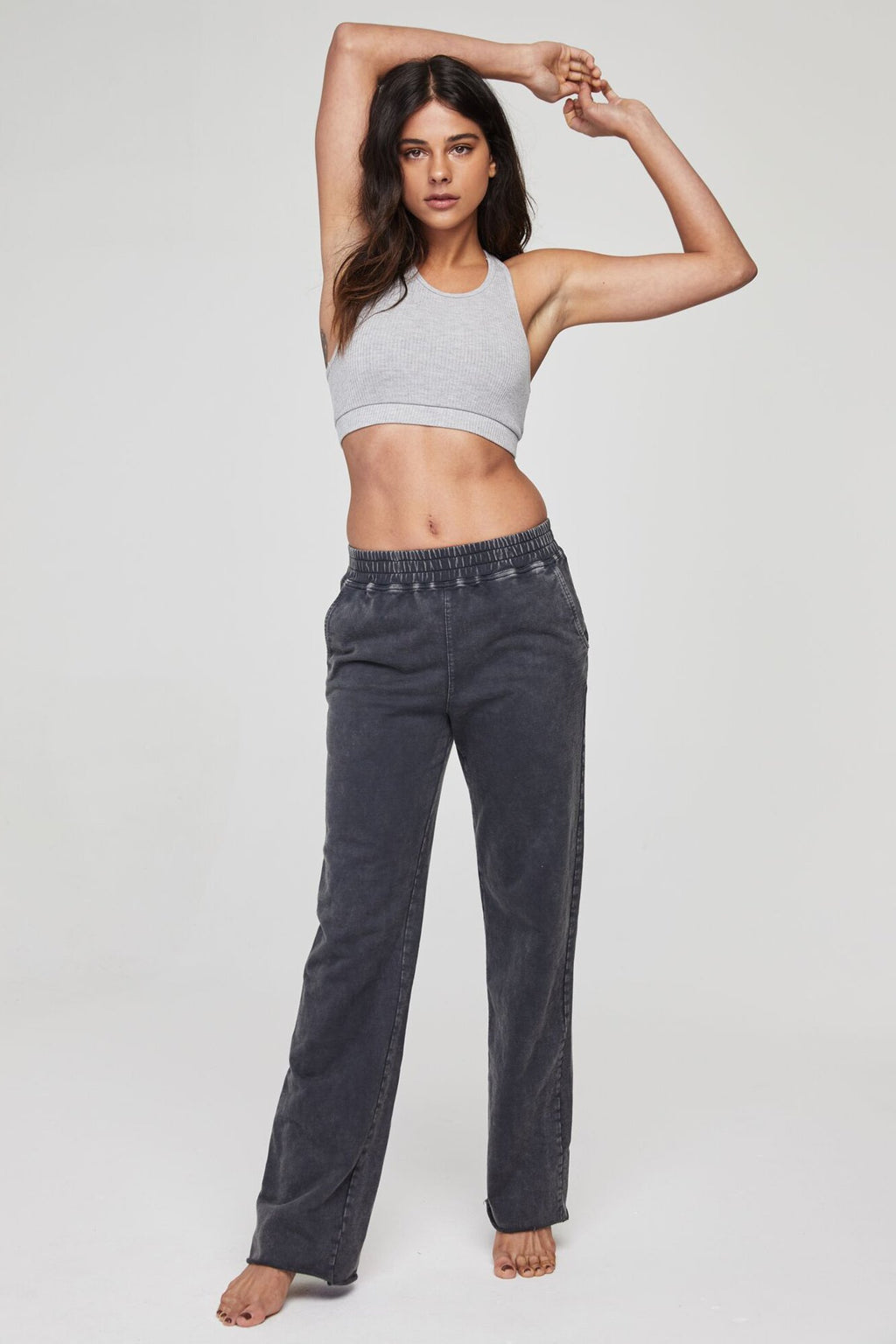 Model is wearing dark grey, high-waist, wide leg spiritual gangster sweat pants. The high waist sweatpant comes with raw edge hem and elastic tie waist.