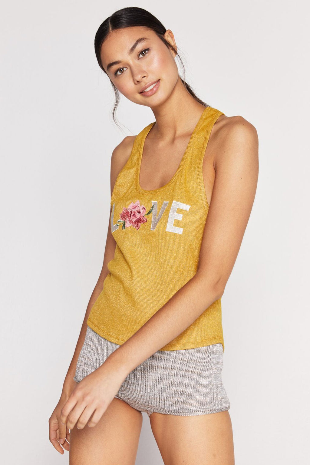 "Model is wearing a yellow scoop neck spiritual gangster tank top. Love floral sparkle tank comes with sparkle detailing throughout and script that reads ""love"". The o in the word ""love"" is a rose with leaves."