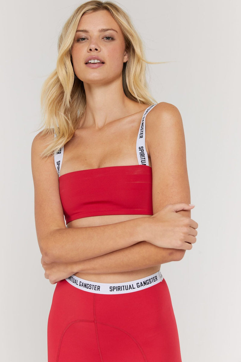 "Model is wearing a crimson red, spandex, bandeau style spiritual gangster sports bra. The Skylar frame bra in crimson comes White straps read ""spiritual gangster"" on each side."