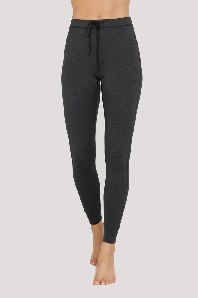 Model is wearing dark heathered grey spiritual gangster leggings. The Maya mid rise active legging comes with a tie-waist.