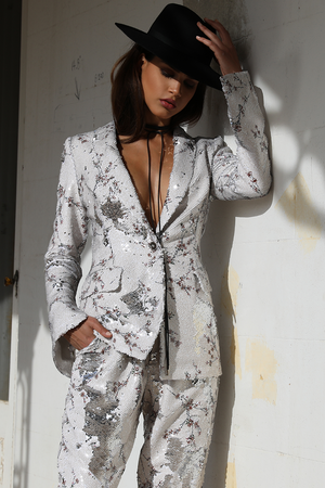 Model is wearing the Rodeo Sequin Blazer by Prem. Bridal wear: Model wears a full sequinned blazer with small cherry blossom detailing