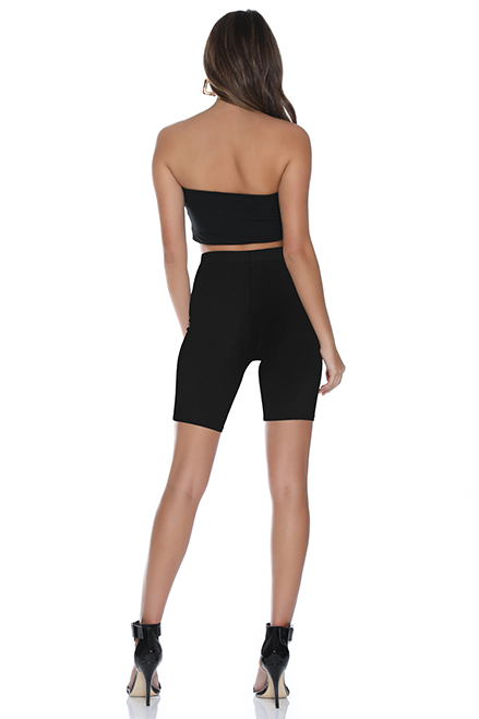 Back view of model wearing black, spandex bicycle shorts with a high waist and a hem that cuts just above the knee.