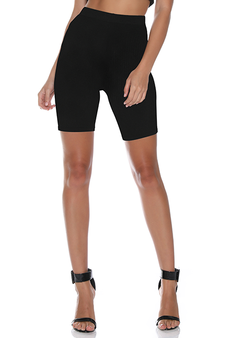 Front view of model wearing black, spandex bicycle shorts with a high waist and a hem that cuts just above the knee.