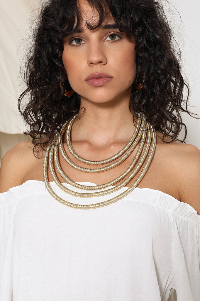 Model wearing the Nala Necklace designed by Prem that features 5 layers of golden thick necklace.