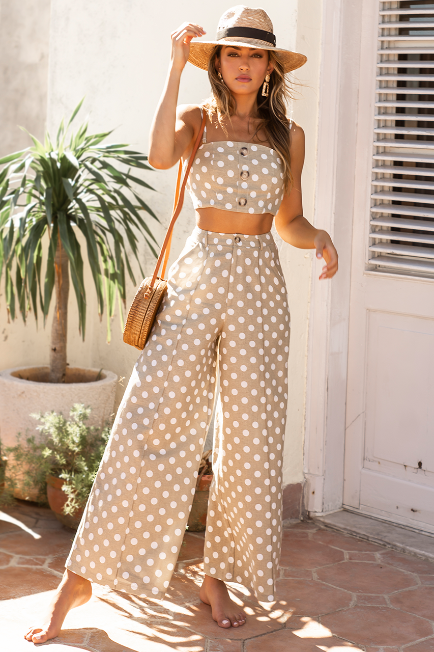 Model is wearing the why hello pants by Prem. The pants are high waisted tan coloured, wide leg pants with a cream polka-dot print all over. Front button closure.