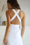 "Bridal wear: Model wears a Seven Wonders square necked white midi dress with a cross back. The ""Fiorella Crossback dress"" has three small gold buttons on either side of the dress which connects the crossed back. the dress feels linen like and the hemline falls just below the knee."