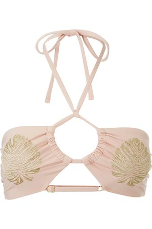 Image shows a Flat lay of a Minkpink nude bikini top, the front of the golden hour ruched halter top features a spaghetti tie halter closure, a key hole with gathering at the centre bust, and two tropical leaves embroidery in gold on the breasts.