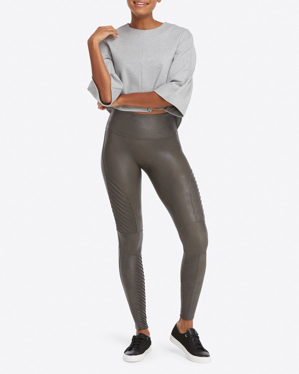 UNIKONCEPT Lifestyle boutique: Model wearing gunmetal moto, slimming Spanx leggings in faux leather fabric. The Moto leggings  details include ribbing along legs.