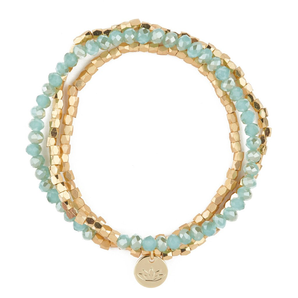 UNIKONCEPT lifestyle boutique: Image shows a gold and aquamarine blue beaded bracelet. The Luv & Bart Zoe bracelet in aqua is a wrap around bracelet with a small gold pendant in the middle of the lotus flower; the brands signage.