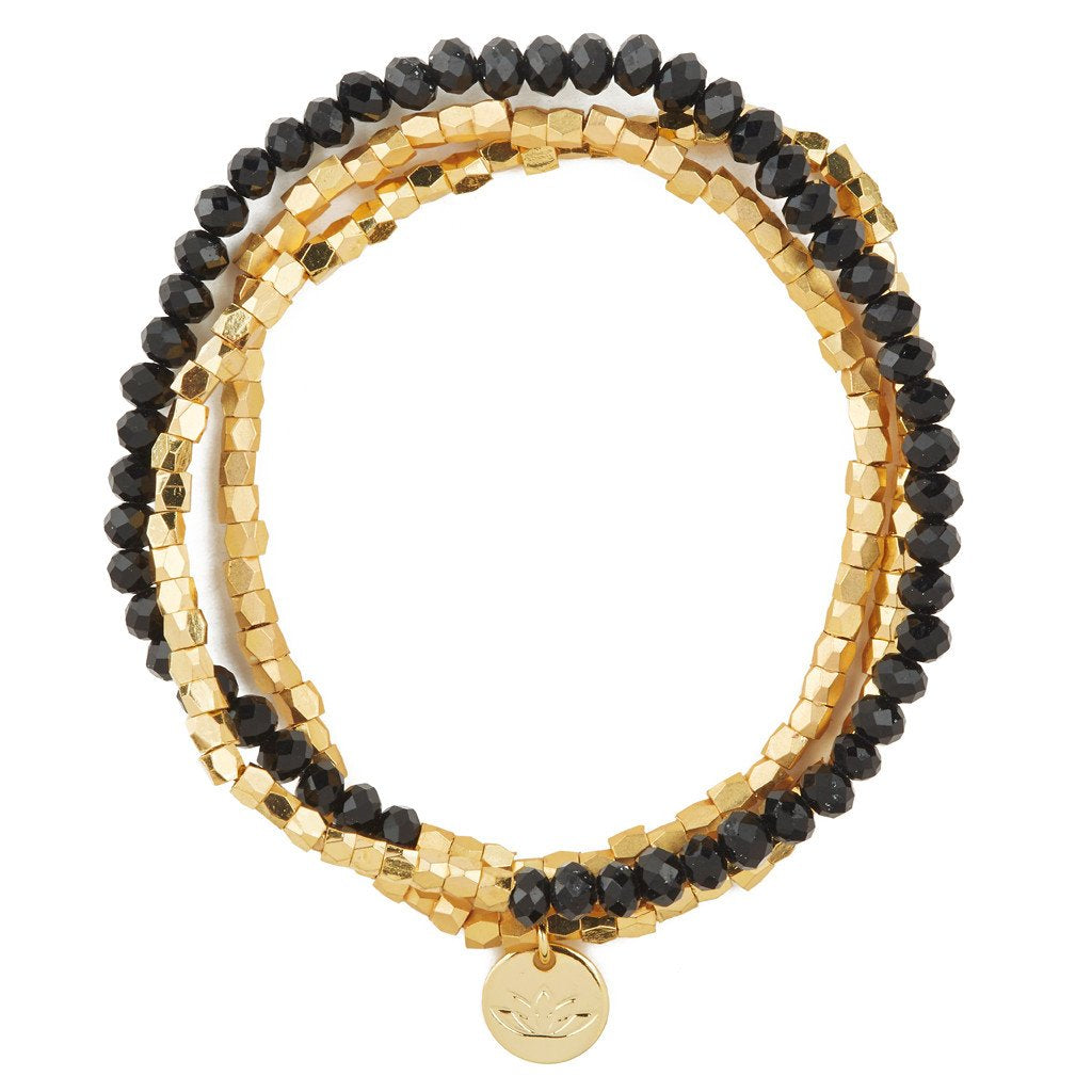 UNIKONCEPT lifestyle boutique: Image shows a gold and black beaded bracelet. The Luv & Bart Zoe bracelet in black is a wrap around bracelet with a small gold pendant in the middle of the lotus flower; the brands signage.