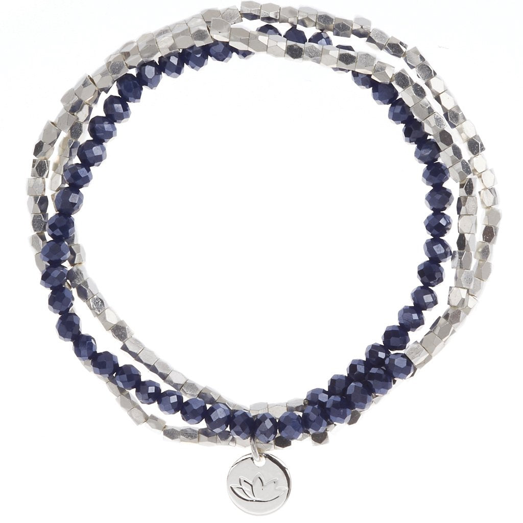UNIKONCEPT lifestyle boutique: Image shows a silver and navy blue beaded bracelet. The Luv & Bart Zoe bracelet in midnight is a wrap around bracelet with a small silver pendant in the middle of the lotus flower; the brands signage.
