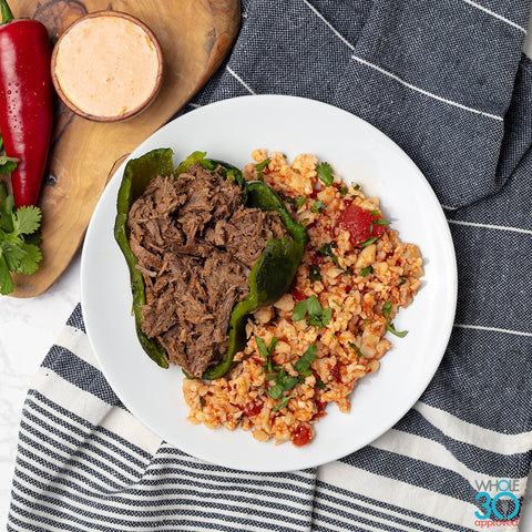 100% grass-fed barbacoa stuffed poblano peppers with chipotle cream + spanish cauliflower rice